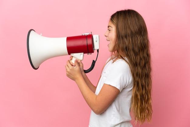 측면 위치에서 뭔가를 발표하기 위해 확성기를 통해 외치는 격리 된 분홍색 배경 위에 아이