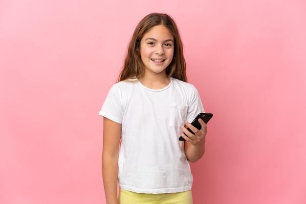 携帯電話を使用して孤立したピンクの背景上の子