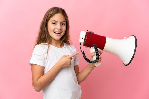확성기를 들고 측면을 가리키는 격리 된 분홍색 벽에 아이