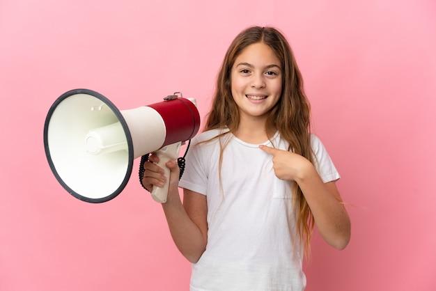 확성기를 들고 깜짝 표정으로 고립 된 분홍색 벽 위에 아이