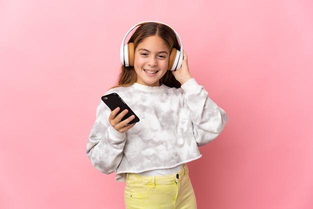 携帯電話で音楽を聴いて歌う孤立したピンクの壁の上の子供