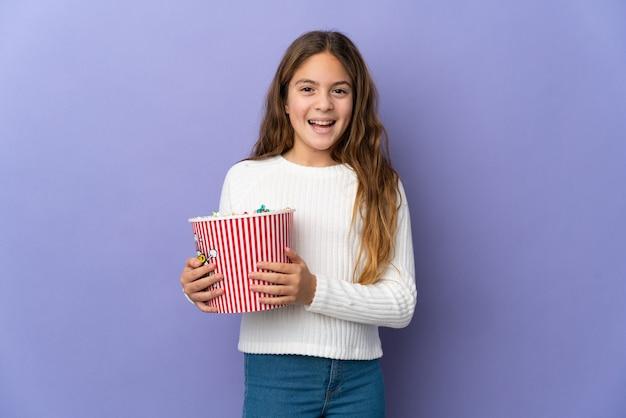 Ребенок на изолированном фиолетовом фоне держит большое ведро попкорна