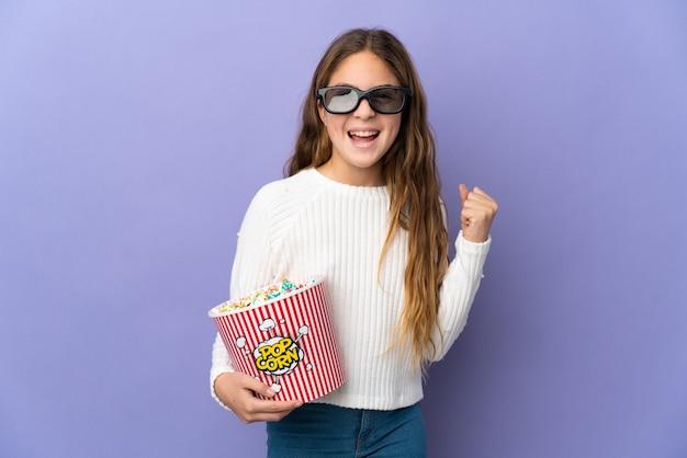 3dメガネとポップコーンの大きなバケツを保持している孤立した紫色の背景の上の子