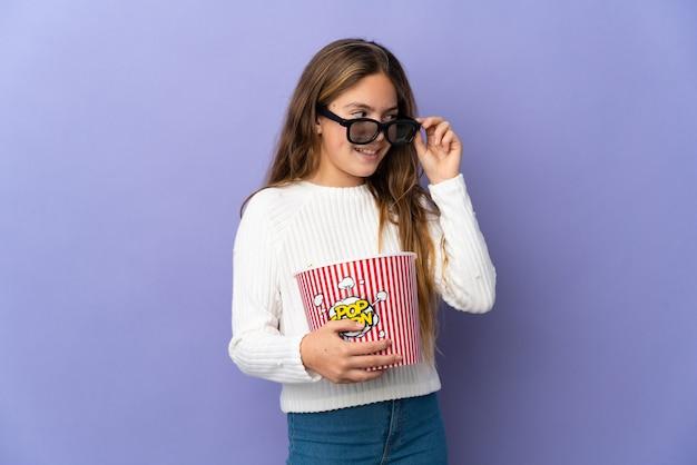 고립된 보라색 배경 위에 3d 안경을 쓰고 큰 팝콘 양동이를 들고 있는 아이
