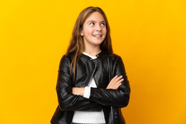Ребенок на изолированном желтом фоне, глядя вверх, улыбаясь