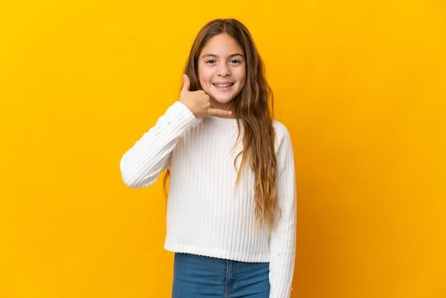 Ребенок на изолированном желтом фоне, делая телефонный жест. перезвони мне знак