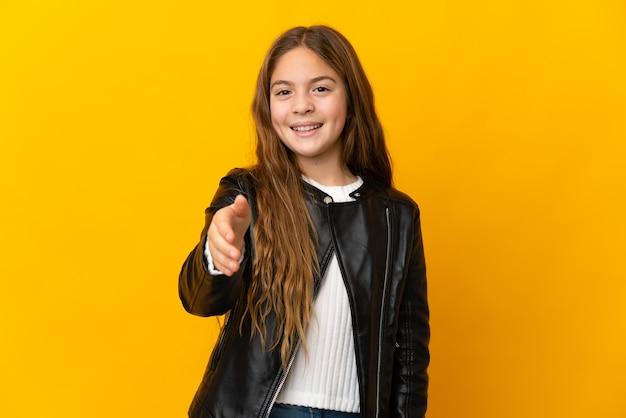 Ребенок на изолированном желтом фоне, пожимая руку для заключения хорошей сделки