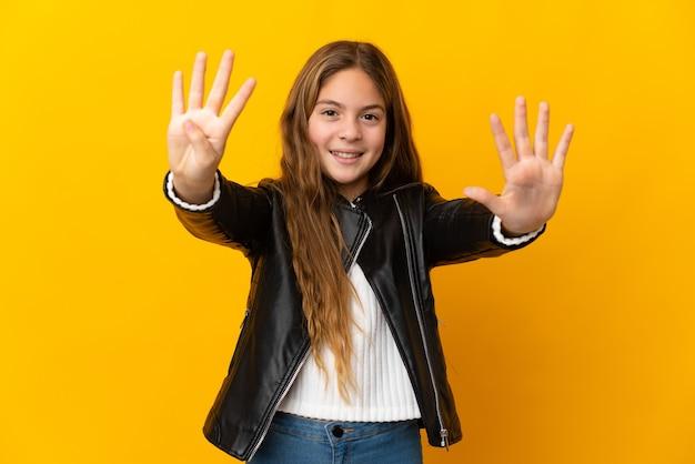 Ребенок над изолированной желтой стеной, считая девять пальцами