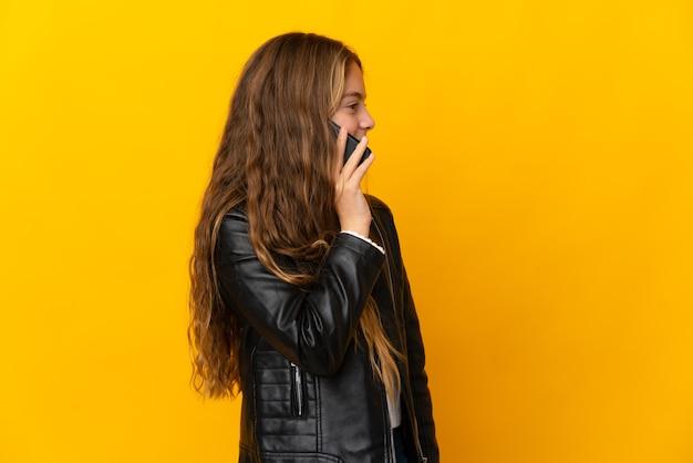 누군가와 휴대 전화로 대화를 유지하는 고립 된 노란색 벽 위에 아이