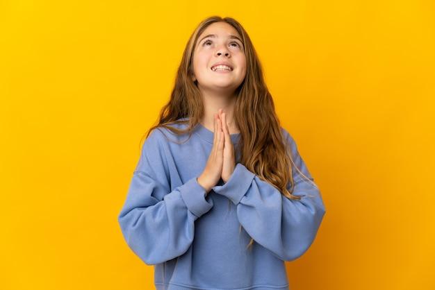 孤立した黄色の壁の上の子供は手のひらを一緒に保ちます。人は何かを求めます