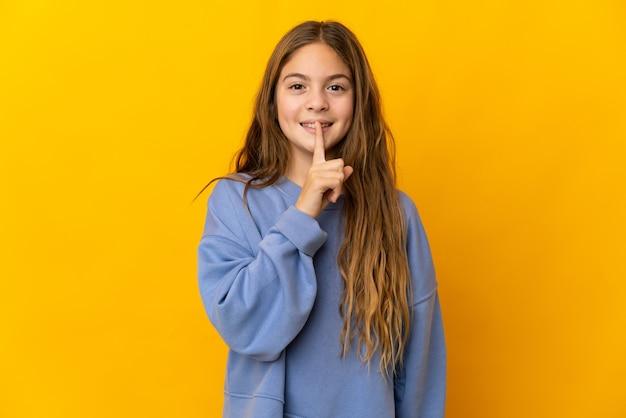 입에 손가락을 넣어 침묵 제스처의 표시를 보여주는 고립 된 노란색 벽 위에 아이