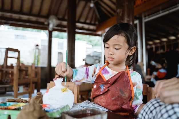 Child painting ceramic pot with paint brush