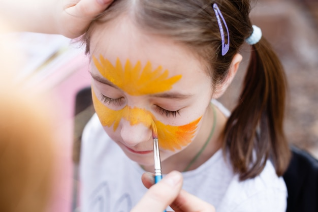 Child painting process on girl's face