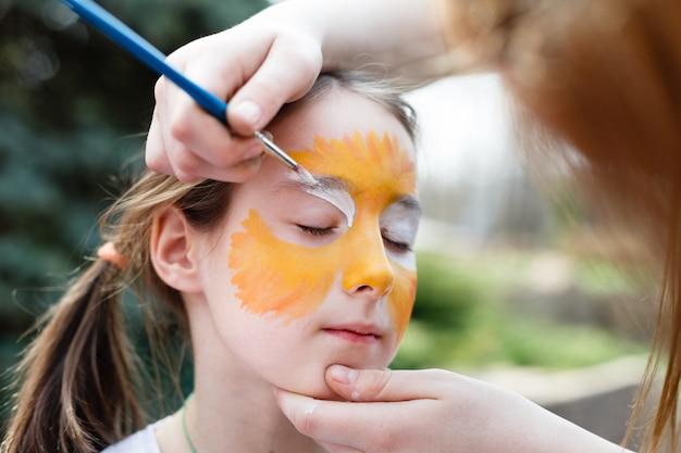 Процесс рисования ребенка на лице девушки