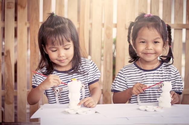 Ребенка живопись, две девочки, с удовольствием нарисовать на штукатурке куклы вместе
