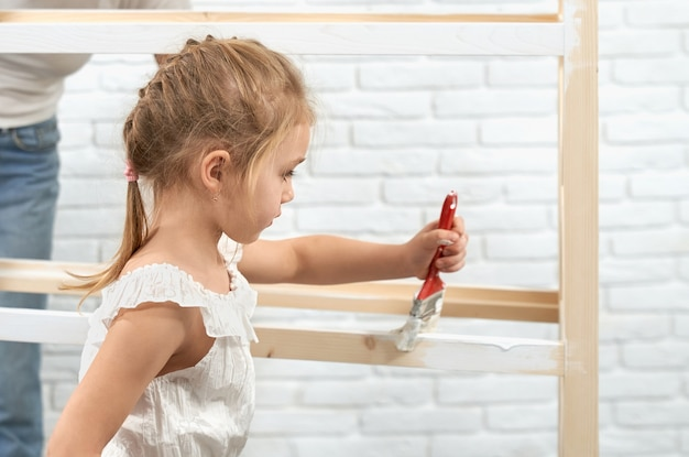 Child painting wooden shelves with brush and white color
