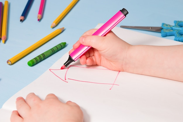 Ребенок рисует дом в альбоме, место для копирования, занятия для детей на синем фоне