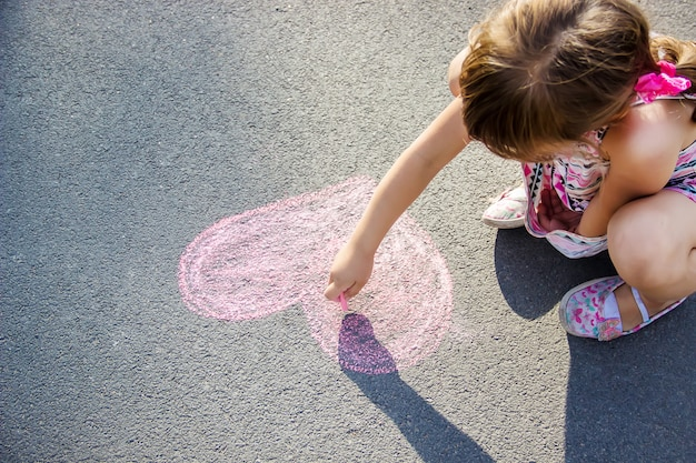 The child paints chalk on the asphalt heart. selective focus.