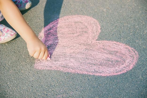 The child paints chalk on the asphalt heart. selective focus.