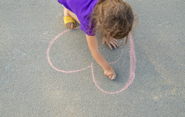 The child paints chalk on the asphalt heart