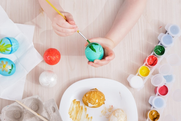 Ребенок раскрашивает пасхальные яйца сидя за столом