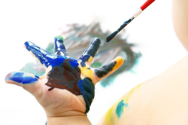 아이는 페인트로 손을 그립니다. 창의력과 예술적 취미