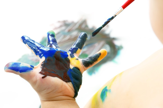 Child paints with paint your hand. creativity and artistic hobby