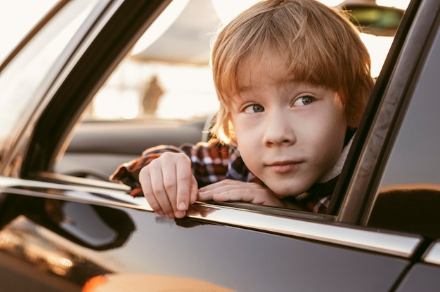 Child peeking his head out the window of a car while on road trip
