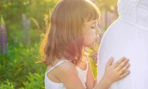 Детская фотосессия в люпиновом поле с беременной матерью