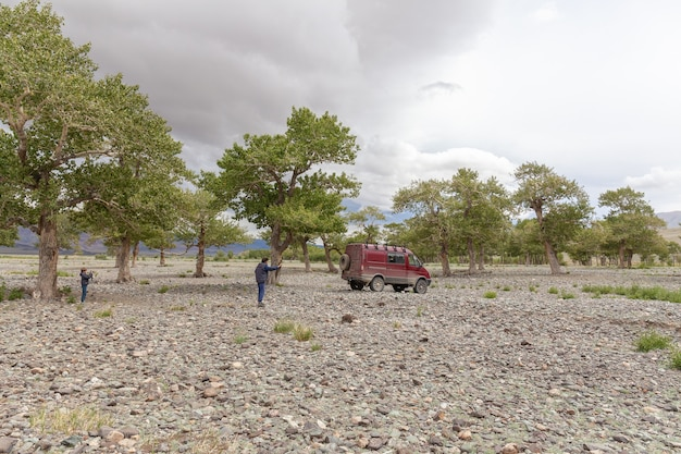 A child photographs a dad who photographs a car on the background of the mountains of mongolia