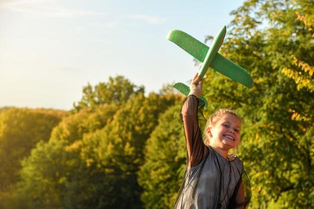 Детский летчик-пилот с мечтой о летнем путешествии на природе на закате. дети счастливо бегают вместе в прекрасную солнечную погоду в парке.