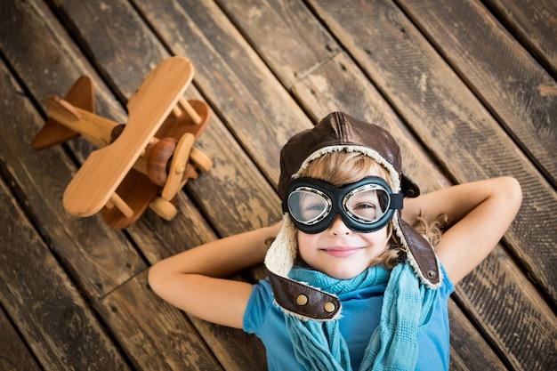 그런 지 나무 배경에 빈티지 비행기 장난감을 가진 어린이 조종사