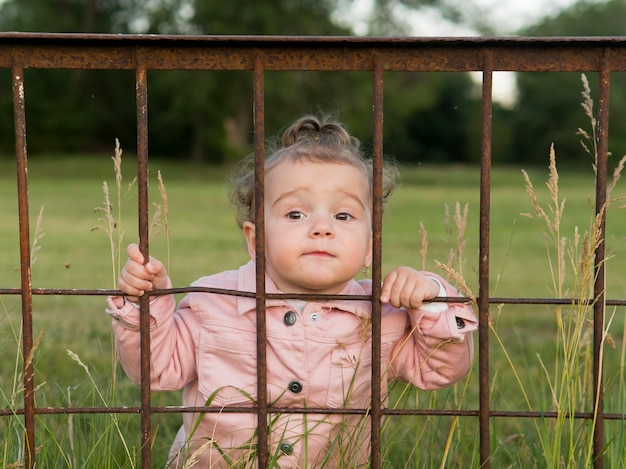 Child in pink clothes behind park bars front view