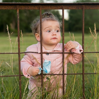 Child in pink clothes behind park bars holding medical mask