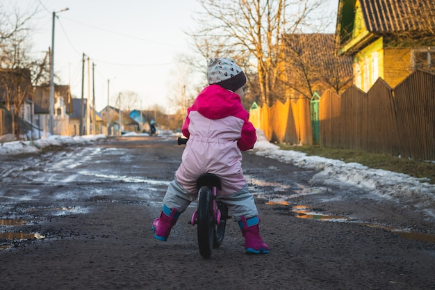Child in pink jumpsuit rides balance bike on dirt road in countryside