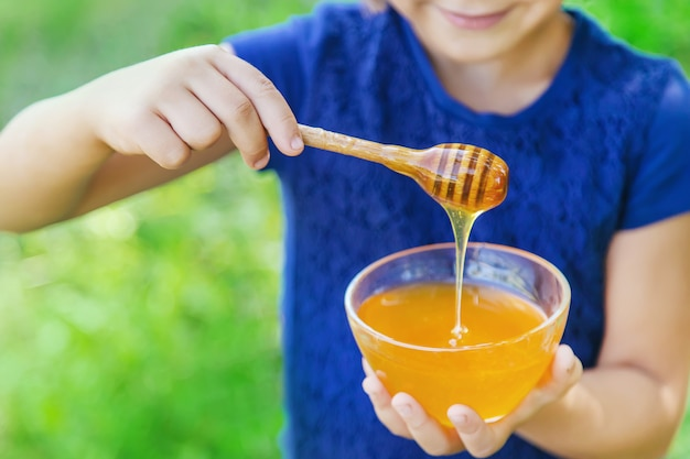 Child a plate of honey in the hands