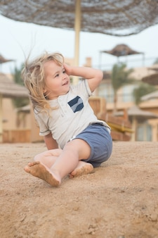 Детская игра босиком на песчаном пляже в солнечный день. мальчик со светлыми волосами развлекается на песке. летний отдых, отдых. активность, энергия, досуг. концепция счастливого детства.