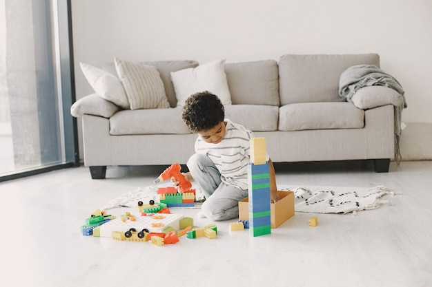 Il bambino gioca con i giochi sul pavimento. il bambino africano compone un costruttore. capelli ricci in un ragazzo.