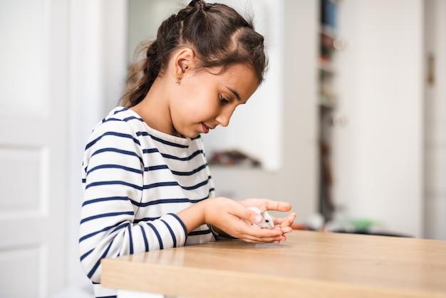 Детская игра с красивым хомяком белого карлика. малыш держит и гладит маленькое домашнее животное. дети и домашние животные вокруг дома