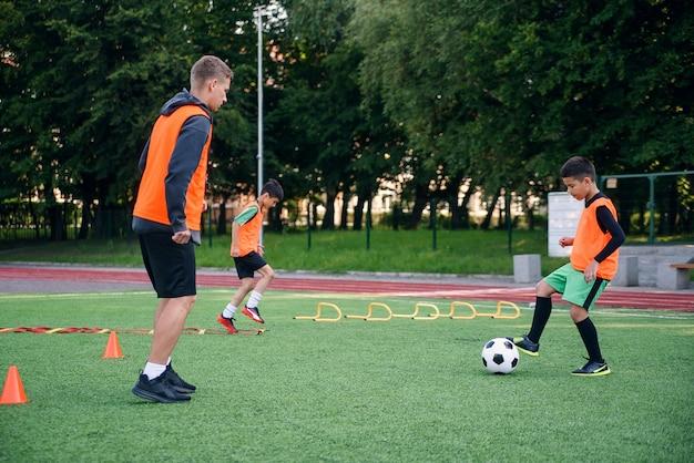 コーチと一緒にキックボールを練習するサッカーユニフォームの子供プレーヤー