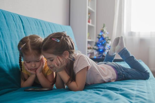 携帯電話のタブレットの子供とスマートフォンで遊ぶ子供