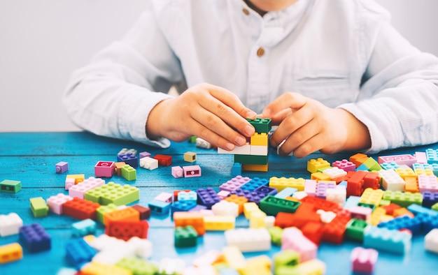 テーブルの上にカラフルなおもちゃのレンガやプラスチックのブロックで遊んで構築している子供。学校または就学前の背景。家庭やクラスでの子供の余暇と教育、早期学習と発達の概念。