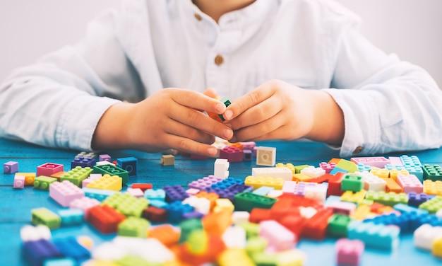 テーブルの上にカラフルなおもちゃのレンガやプラスチックのブロックで遊んで構築する子供