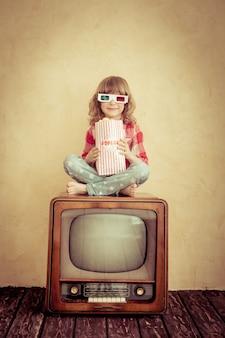 Ребенок играет дома. ребенок сидит на ретро-телевизоре и ест попкорн. концепция кино