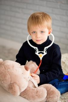おもちゃで医者をしている子供。就学前および幼稚園の子供のための小児科医。小児科、ヘルスケアおよび人々の概念。