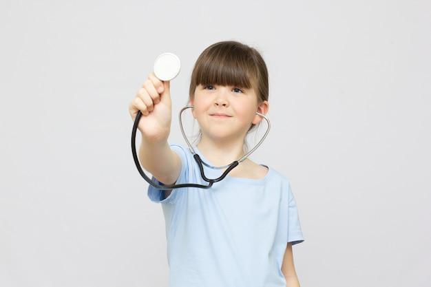 Ребенок играет доктора со стетоскопом в руках. счастливый улыбающийся ребенок девочка, играющая дома или в детском саду. обучение для дошкольников и детских садов. концепция педиатрии, здравоохранения и людей.