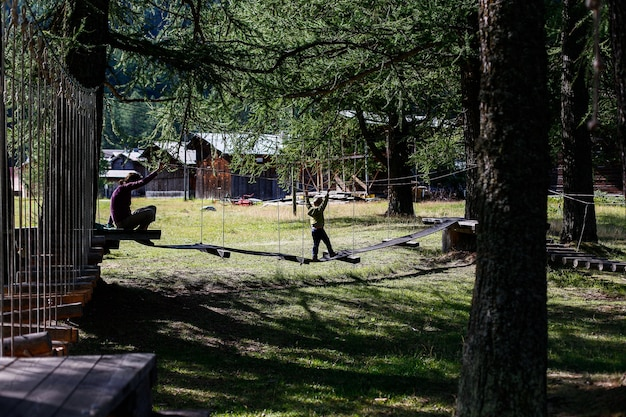 Child playing in a family adventure park in a european forest.