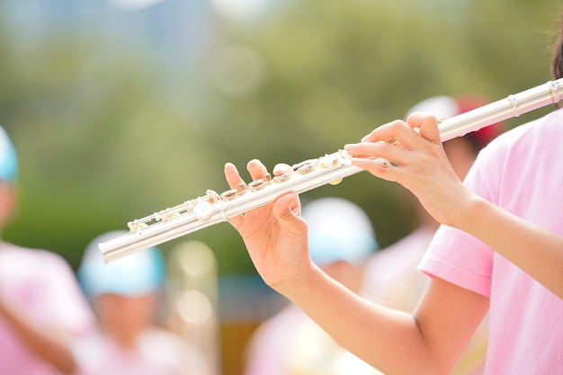 Child playing flute at the sports day of elementary school