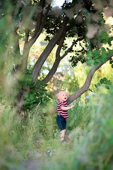 A child playing in a green forest in summer