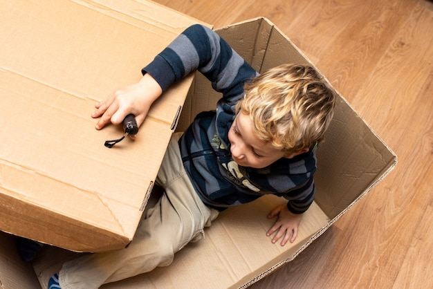 Child playing inside a cardboard box.